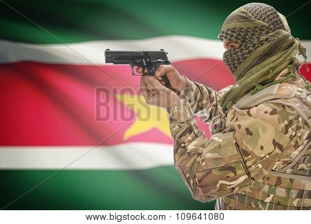 Male In Muslim Keffiyeh With Gun In Hand And National Flag On Background - Suriname