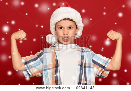 winter holiday christmas concept - boy in santa hat show muscle on red background