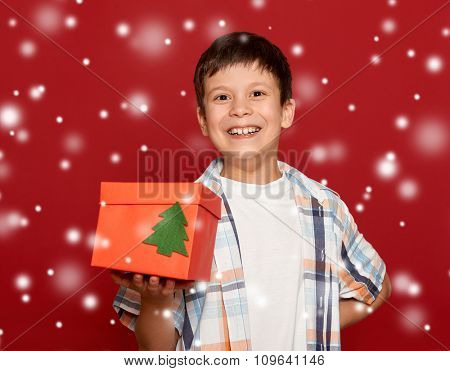 winter holiday christmas concept - boy with box gift on red background