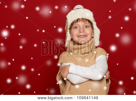 winter, child,  concept - happy girl in hat and sweater posing on red background