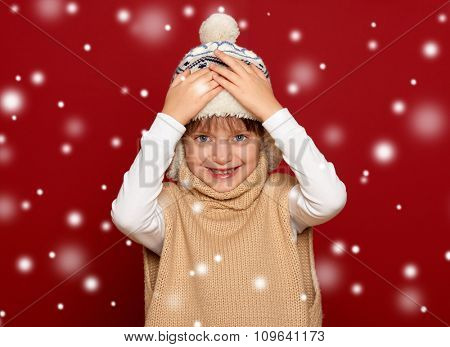 winter, child,  concept - happy girl in hat and sweater on red background