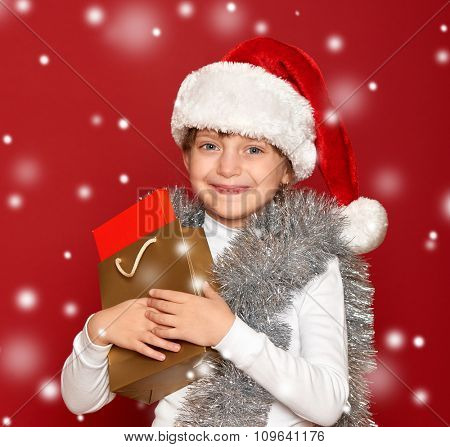 winter, child,  christmas concept - happy girl in santa hat with box gift on red background