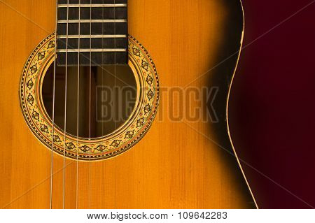 Old guitar close up isolated on a burgundy background