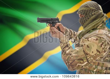 Male In Muslim Keffiyeh With Gun In Hand And National Flag On Background - Tanzania