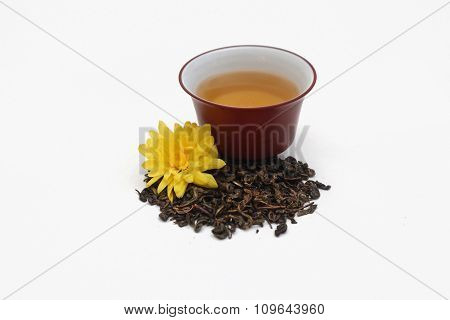 Ceramic gaiwan full of green tea  and a pile tea leaves with yellow flower