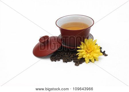 Ceramic gaiwan with green tea and a pile tea leaves with yellow flower