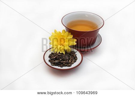 Ceramic gaiwan with green tea and tea leaves with yellow flower  in a bowl