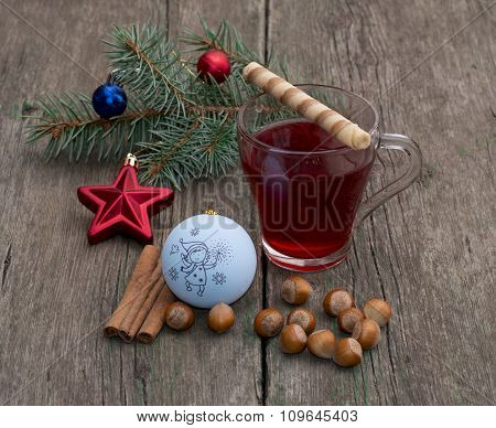 Coniferous Branch With Christmas Tree Decorations, Tea, A Star, Nutlets And Baking