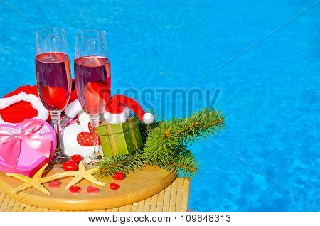 Glasses With Red Champagne  And Christmas Decor On Swimming Pool Background