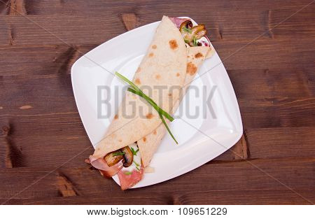 Flatbread with bacon and mushrooms on wood from above