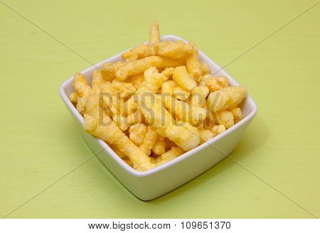 Snack corn cheese into square bowl of green