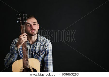 Young man with guitar on dark background