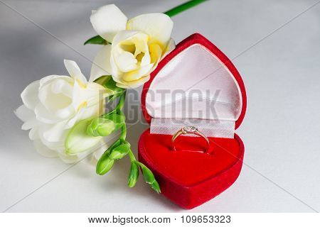 Golden Engagement Ring In A Heart Shaped Box And A Flower Freesia
