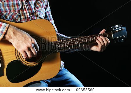 Young man playing on guitar close up