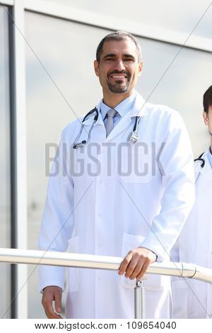 Handsome smiling doctors standing in a row near the clinic