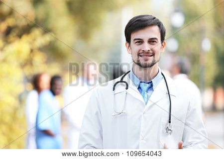 Smiling doctor with medical stuff behind, outdoors