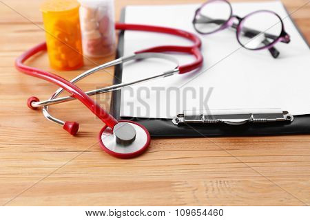 Medical stethoscope with clipboard and pills on wooden table close up