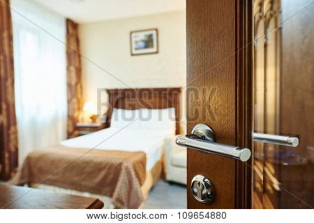 Hotel room or apartment doorway with open door and bedroom in background