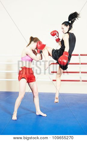 Muay thai female boxers fighting at training boxing ring