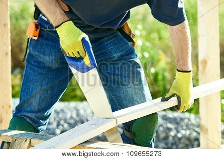 Closeup construction roofer carpenter worker sawing wood board with hand saw outdoors