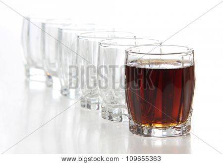 Glass cups with whiskey on white background