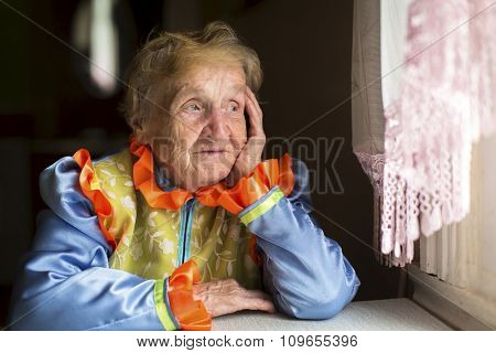 Elderly woman sadly looking out the window.