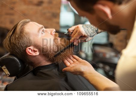 Cheerful young bearded man at hair salon