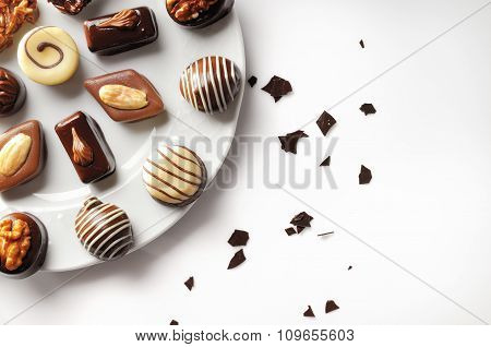 Assorted Bonbons On A White Plate Top View