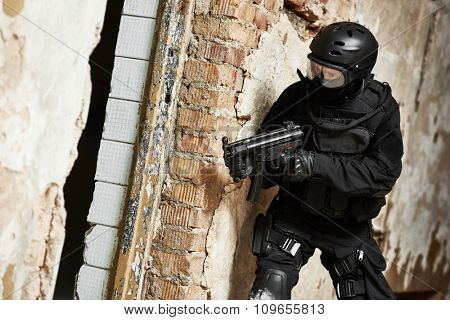 Military industry. Special forces or anti-terrorist police soldier, private military contractor armed with machine gun ready to attack during clean-up operation