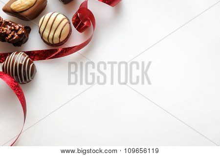 Assorted Bonbons With Red Ribbon On A White Table Top