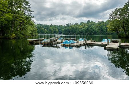Aluminium bass fishing boat and pedalos at wooden dock in Virginia, America USA