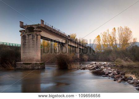 Broken bridge over a river in autumn