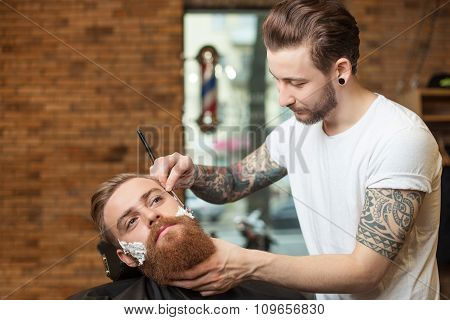 Cheerful young barber is working with shaver