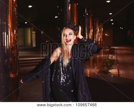 Happy stylish woman poses on the street at night