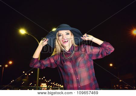 Happy stylish woman in hat  poses on the bridge at night