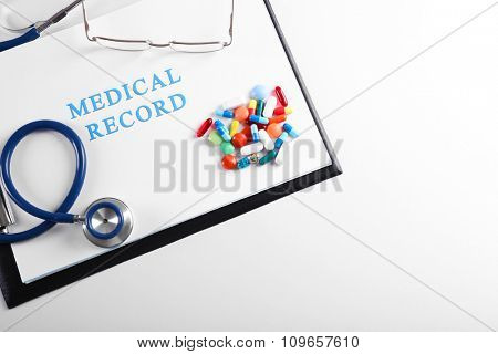 Stethoscope with medical record and pills isolated on white