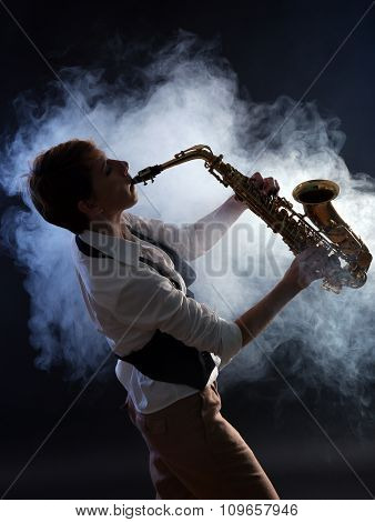 Attractive woman plays saxophone on dark background in the smoke