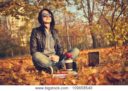 Girl With Coffee Cup Sitting On Leaves In Park