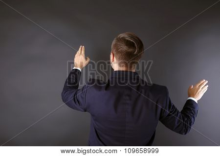 Back view of Caucasian young man in a navy blue suit pointing on dark grey background