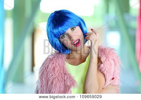 Young woman with blue hairstyle inside the building