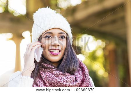 Portrait Of Woman With Cap Talking By Smart Phone, Outdoor.