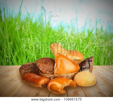 Fresh bread on wooden table, on nature background