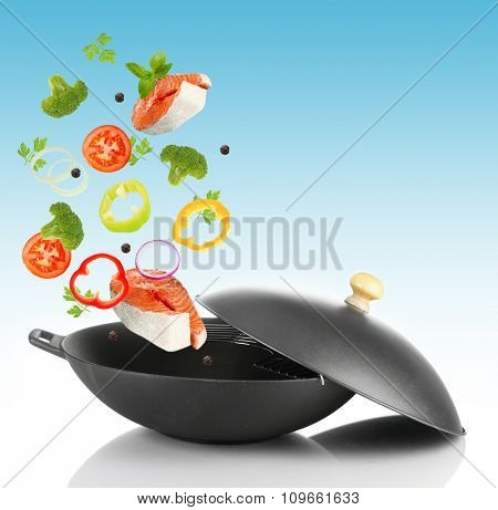 Fresh vegetables falling in the frying pan on light blue background