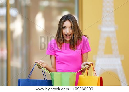 Beautiful young woman with shopping bags near showcases outdoors