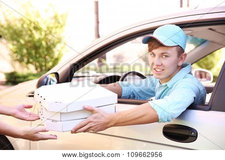 Pizza delivery boy  with pizza box in car, close-up