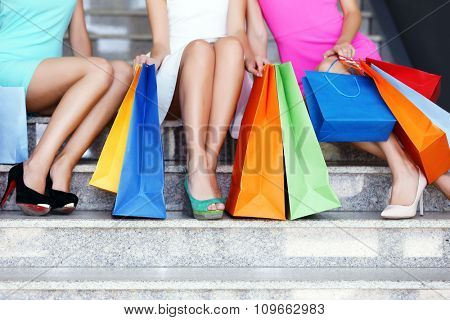 Beautiful young women with shopping bags sitting on steps