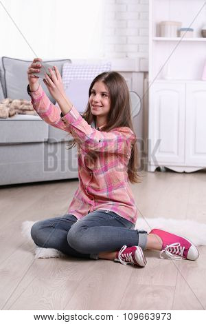 Young pretty girl sitting on the floor and making selfie in her room
