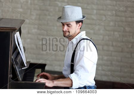 Profile of handsome young man in hat making piano music