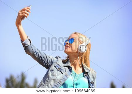 Young woman listening to music and makinf selfie on the sky background
