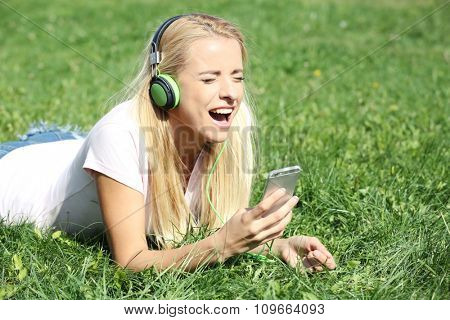 Young woman with earphones and smartphone listening to music on grass